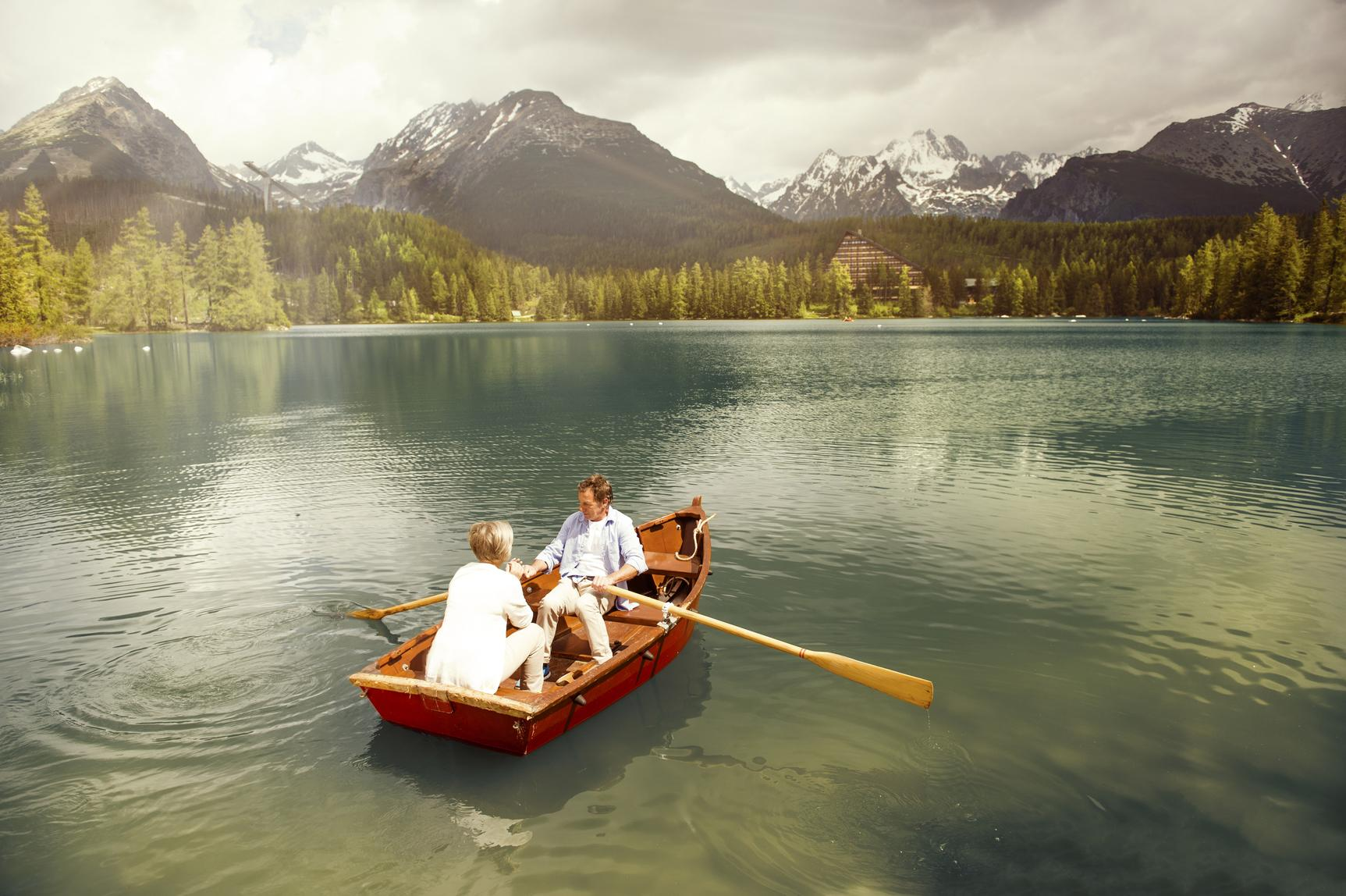 Couple paddling on boat with mountains in the distance